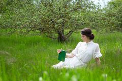 Beautiful woman in white dress with book on summer meadow Royalty Free Stock Images