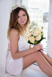 Beautiful woman in white dress with flowers sitting near the win Royalty Free Stock Photo