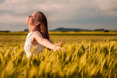 Beautiful woman in white dress on golden yellow wheat field Royalty Free Stock Images