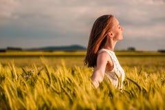 Beautiful woman in white dress on golden yellow wheat field Stock Photo