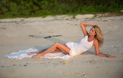 Beautiful woman in white dress lying on the beach Royalty Free Stock Images