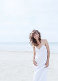 Beautiful woman in a white dress on the ocean coast. Happy girl on the beach, the wind fluttering hair. Royalty Free Stock Image