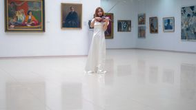 Beautiful woman in a white dress is playing the violin in the gallery stock video