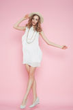 Beautiful woman in white dress posing on pink background in hat Stock Image