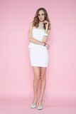 Beautiful woman in white dress posing on pink background royalty free stock photos
