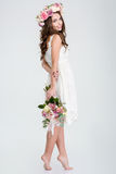 Beautiful woman in white dress and roses wreath standing barefoot. Full length of beautiful smiling young woman in white dress and wreath of roses standing Stock Image