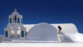 Beautiful woman with a white dress and a scarf in front of a white church stock image