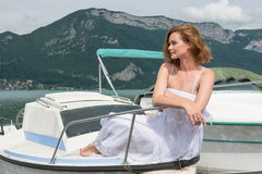 Beautiful woman in white dress sitting on a boat and looks away. Stock Photography