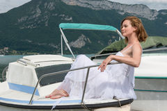 Beautiful woman in white dress sitting on a boat and looks away. Royalty Free Stock Photo