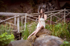 Beautiful woman in white dress sitting at nature Royalty Free Stock Photo