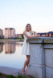 Beautiful woman in a white dress standing on the waterfront Stock Photo