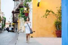 Beautiful woman on white dress walking alone at the colorful streets of the colonial walled city of Cartagena de Indias. A Beautiful woman on white dress walking stock photos