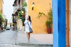 Beautiful woman on white dress walking alone at the colorful streets of the colonial walled city of Cartagena de Indias. A Beautiful woman on white dress walking stock images