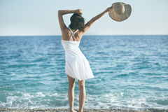Beautiful woman in a white dress walking on the beach.Relaxed woman breathing fresh air,emotional sensual woman near the sea Royalty Free Stock Image