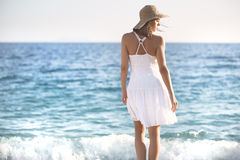 Beautiful woman in a white dress walking on the beach.Relaxed woman breathing fresh air,emotional sensual woman near the sea, enjo. Ying summer.Travel and Royalty Free Stock Images