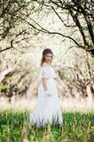 Beautiful woman in white dress walking in park Stock Images