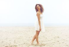 Beautiful woman in white dress walking on sand at the beach Royalty Free Stock Photography