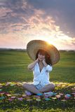 Beautiful woman in white dresses. And big hat with beautiful nature on sunset times royalty free stock images