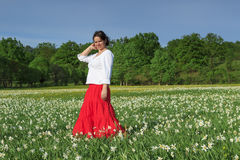 Beautiful woman in a white flowers field. Young happy woman in a white daffodil flowers field Royalty Free Stock Images