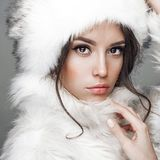 Beautiful woman in white fur coat and fur hat. Fashion studio portrait of beautiful lady in white fur coat and fur hat. Winter beauty in luxury. Fashion fur Stock Images