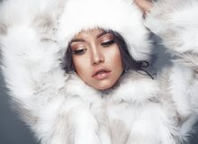 Beautiful woman in white fur coat and fur hat. Fashion studio portrait of beautiful lady in white fur coat and fur hat. Winter beauty in luxury. Fashion fur Royalty Free Stock Photo
