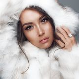 Beautiful woman in white fur coat and fur hat. Fashion studio portrait of beautiful lady in white fur coat and fur hat. Winter beauty in luxury. Fashion fur Stock Image