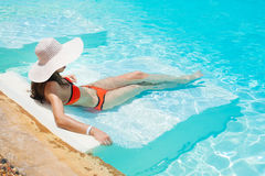 Beautiful woman white hat and bikini lying in a pool Royalty Free Stock Images