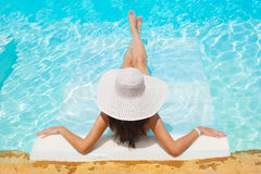 Beautiful woman white hat and bikini lying in a pool Royalty Free Stock Photo