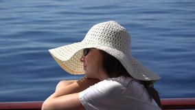 Beautiful woman with white hat have a cruise on blue sea. UHD 4K stock footage