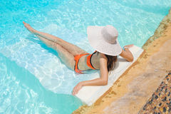 Beautiful woman in white hat lying in a pool Royalty Free Stock Photos