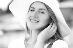 Beautiful woman in white hat with toothy smile posing on beach Royalty Free Stock Images