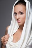 Beautiful woman in white hood isolated on grey. Royalty Free Stock Photo
