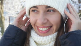 Beautiful woman in white knitted hat listening to music on headphones.  stock footage