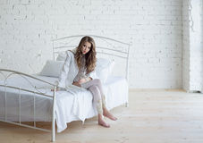 Beautiful woman in white lingerie on white bed Royalty Free Stock Photography