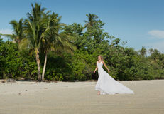 Beautiful woman in white long dress runs at the beach Royalty Free Stock Image