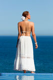 Beautiful Woman in white. Oasis of Calm. Young woman in white at the edge of the pool looking the sea Royalty Free Stock Photos
