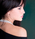 Beautiful woman with white pearl looking back stock photos