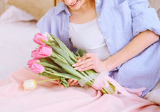 Beautiful woman with white and pink tulips. Smiling on the bed stock photos