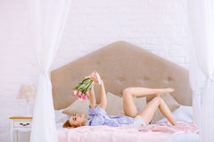 Beautiful woman with white and pink tulips. Smiling on the bed stock images