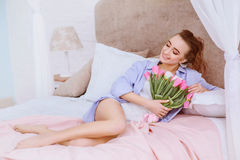 Beautiful woman with white and pink tulips. Smiling on the bed royalty free stock photography