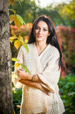Beautiful woman in white posing in autumnal park. Young brunette woman spending time in autumn near a tree in forest Stock Images