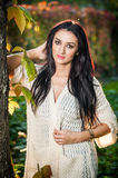 Beautiful woman in white posing in autumnal park. Young brunette woman spending time in autumn near a tree in forest Royalty Free Stock Photos