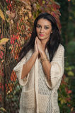 Beautiful woman in white posing in autumnal park. Young brunette woman spending time in autumn near a tree in forest Royalty Free Stock Photography