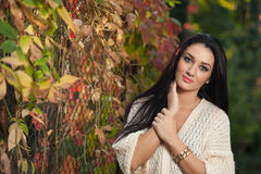 Beautiful woman in white posing in autumnal park. Young brunette woman spending time in autumn near a tree in forest Royalty Free Stock Photo