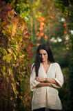 Beautiful woman in white posing in autumnal park. Young brunette woman spending time in autumn near a tree in forest Royalty Free Stock Images
