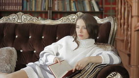 Beautiful woman in white pullover lying on sofa and reading the book. She getting bored and stopping reading stock video