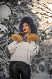 Beautiful woman in white pullover with over-sized fur cap enjoying the winter scenery in forest. Blonde girl posing Royalty Free Stock Images