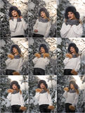 Beautiful woman in white pullover with over-sized fur cap enjoying the winter scenery in forest. Blonde girl posing. Under snow-covered trees branches Stock Photo