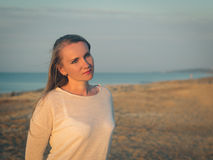 Beautiful woman in white shirt at the evening beach. Stock Photos