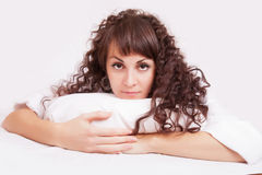Beautiful woman in white shirt lying on a bed Royalty Free Stock Photo